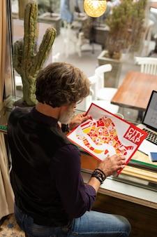 Изучая карту. сосредоточенный бородатый мужчина сидит в кафе и внимательно смотрит на карту города в руках перед прогулкой.