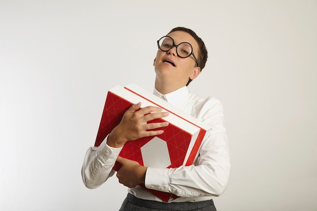 Insegnante femminile caucasico esasperato vestito conservativamente giovane che tiene raccoglitori rossi e bianchi isolati su bianco