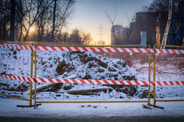 The excavated ground in the snow in winter is fenced with a metal fence with mesh and barrier tape