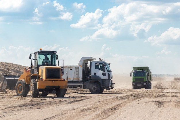 市外の建設現場にある掘削機とダンプトラック。道路は都市間高速道路で機能します