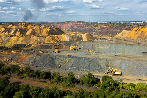 石灰岩の採石場の掘削機と重鉱山のダンプトラック