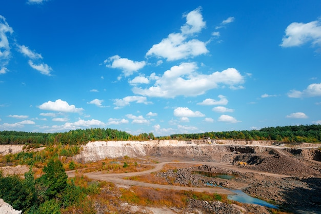 石灰岩採石場の掘削機と大型マイニングダンプトラック