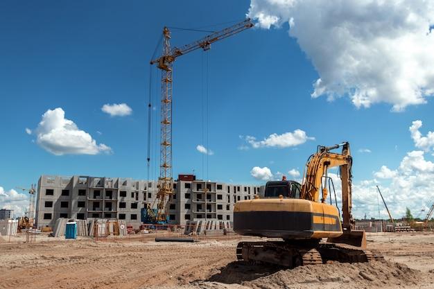 タワークレイを背景に建設現場での掘削機