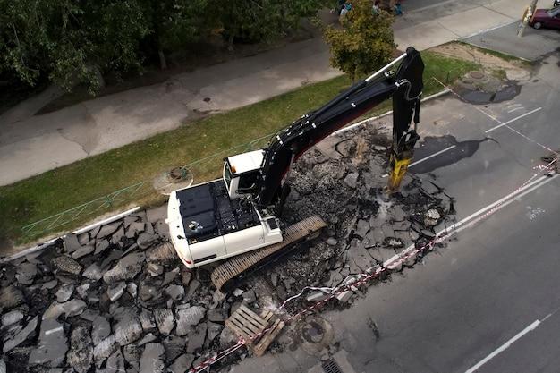 道路工事の修理時にハイドロハンマードリルでコンクリート路面を破壊する掘削機
