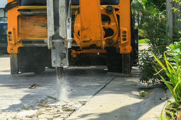 Excavator breaking concrete road surface