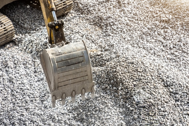 Excavator bucket close up against a background of gray crushed stone.