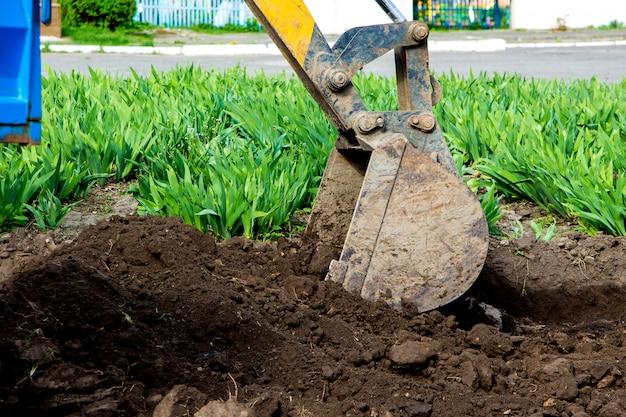 Ковш экскаватора подбирает землю под погрузку