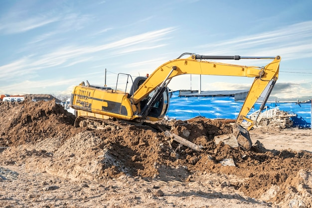 A excavator bulldozer digging dirt ground, shoveling ion the construction site