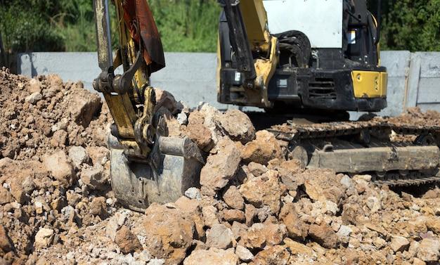 Экскаватор-бульдозер в песочнице, роющей грунт на строительной площадке