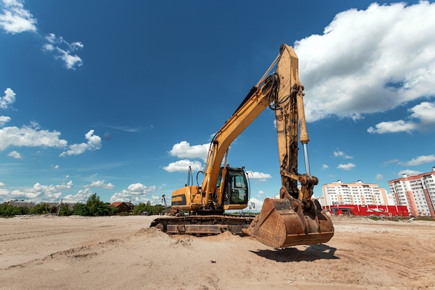 Excavator on a construction site against a blue sky