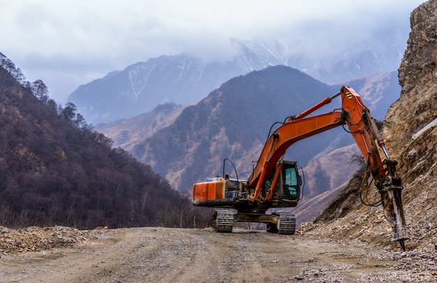 Excavator crushes stones in the mountains