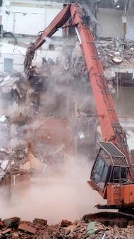 Экскаватор сносит старое здание с помощью специальной техники