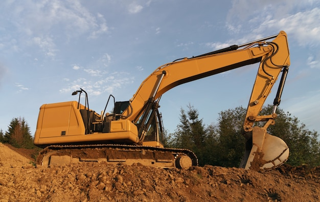 Excavator digging in ground on construction site