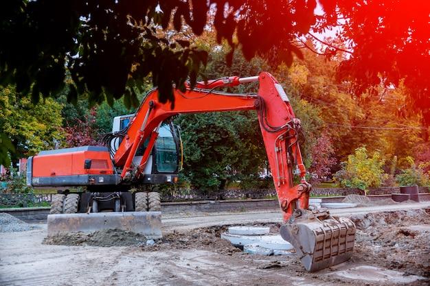 Excavator digging hole, breaking street asphalt, repairing damaged water supply pipe