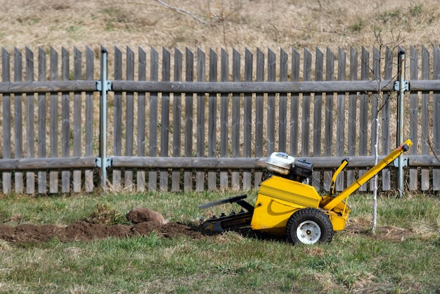 Excavator digging up soil to make watering system for plants.