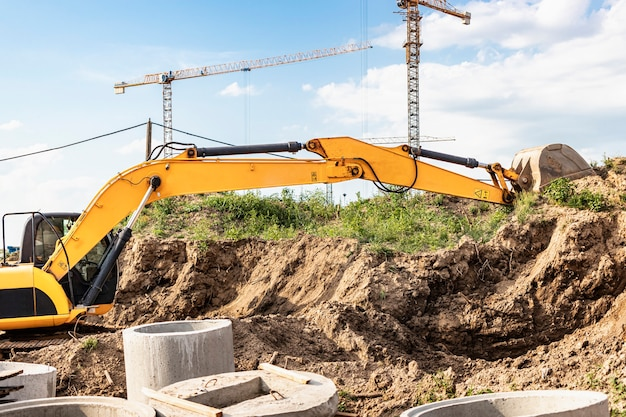 The excavator digs a foundation pit for the installation of sewer wells. tower cranes in the background. excavation works - supplying water and sewerage to residential buildings.