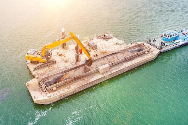 掘削機は川に砂を掘ります。川に重いはしけを押すタグボートの上面図