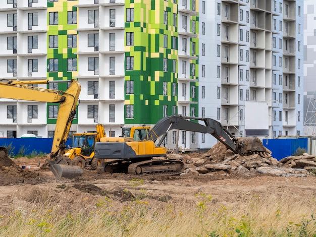 Экскаватор роет землю под фундамент и строительство нового дома.
