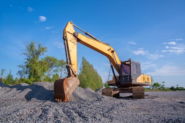 青空の背景に道路建設のための掘削機