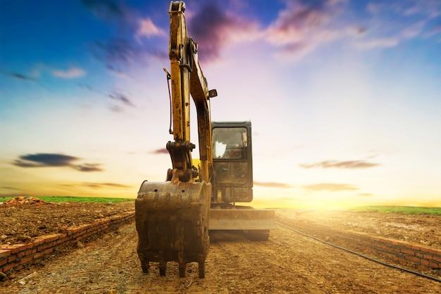 夕焼け空の建設現場での掘削機