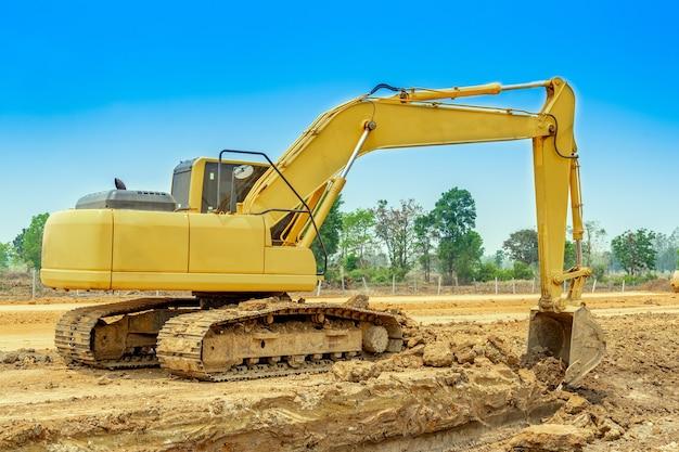 Экскаватор копает почву для расчистки строительной площадки. экскаватор - тяжелая строительная техника, состоящая из стрелы.