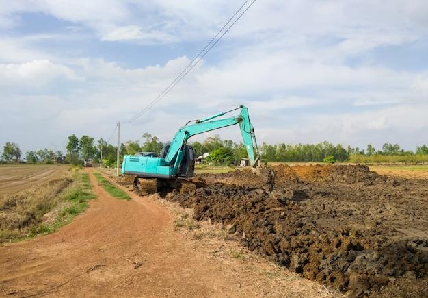 Экскаватор работает на земляных работах для рытья прудов возле рисового поля, хранит воду для использования в сельском хозяйстве летом, вид спереди для копирования пространства.