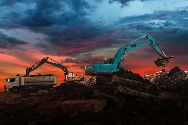 Excavator loader in construction site at sunset sky background