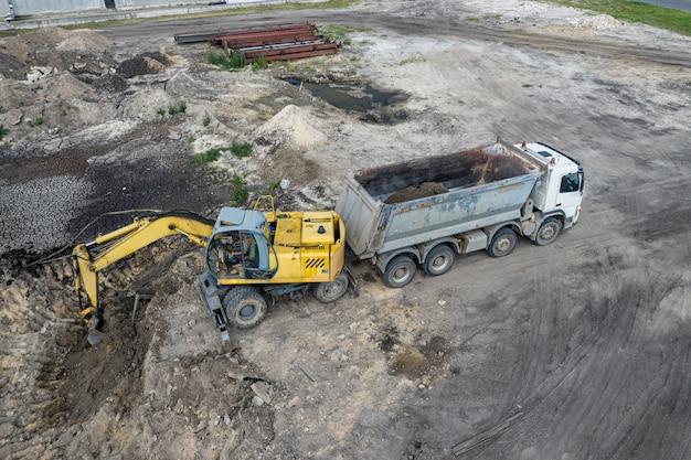 Экскаватор загружает песок в грузовик