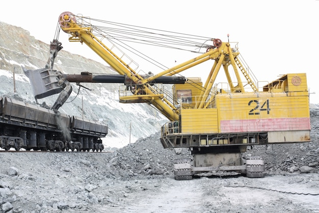 The excavator loads the stones into the cars.