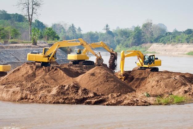 掘削機グループは洪水を保護するために川で働いています