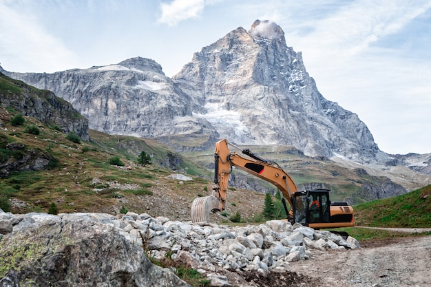 Excavator machine parked on the road with the mountain in the background