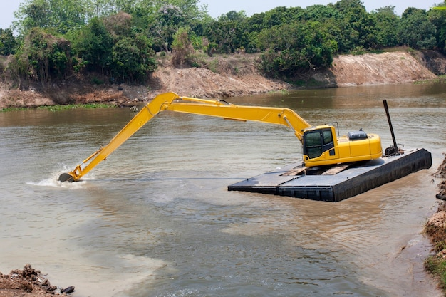 굴삭기 기계는 홍수 보호를 위해 강에서 작동합니다.