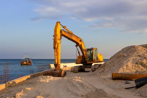 An excavator near the sea digs sand to build a beach on the coastal zone.