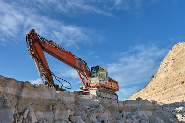 掘削機は石切り場の背景に立っています。