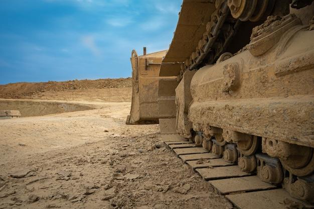 Экскаватор суммирует почву на строительной площадке в сухой летний сезон