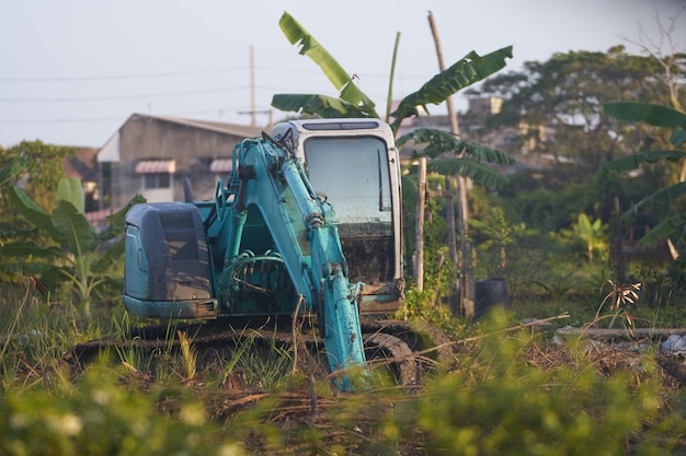 Excavator tractor working on mud soil with tree