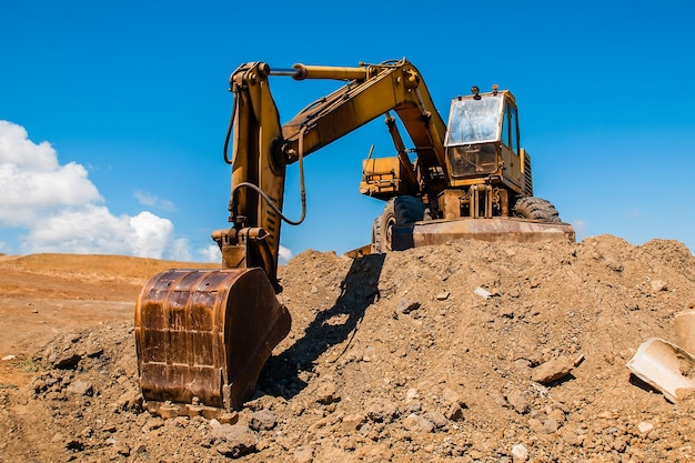 Excavator with bucket standing on soil hill and blue sky background