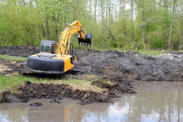 Excavator with long arm in swamp digging river canal in countryside