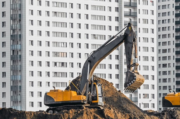 Excavator work on the ground on background of multi storey houses.
