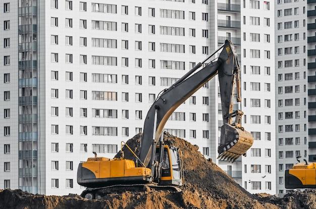 Экскаваторные работы на земле на фоне многоэтажных домов.