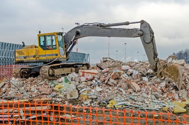 오래된 산업 건물의 철거 작업을 하는 굴착기.