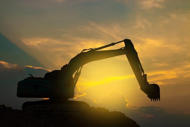 掘削機は夕焼け空に懸命に取り組んでいます。