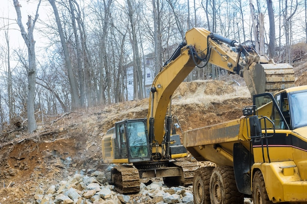 Excavators work with a stone tractor loads trucks stone transports with stone, transporting