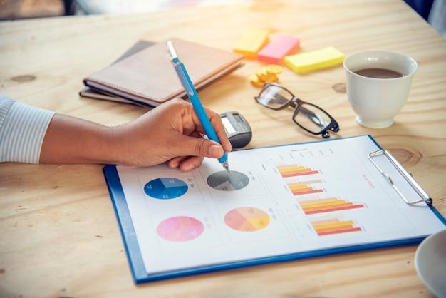 Excel統計スプレッドシートビジネス分析グラフ統計とグラフデータベース内のグラフおよびテーブルデータ番号。会計士の手がエクセル統計財務スプレッドシートドキュメントビジネスグラフグラフを指しています。