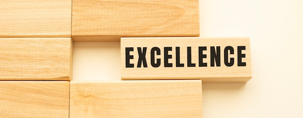 Excellence text on a strip of wood lying on a white table