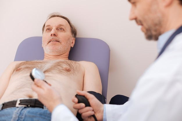 Excellent competent young professional using a special blood pressure monitor while running a general checkup on mans health