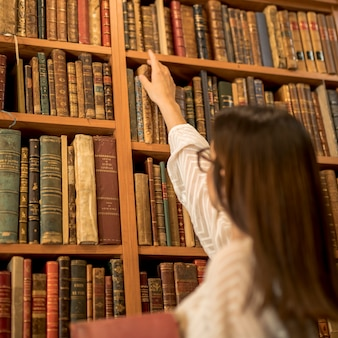 Excellent female student choosing vintage book in library