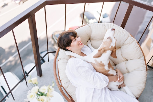 Excellent girl with charming smile enjoys saturday morning on balcony holding funny beagle dog.