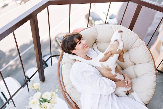 매력적인 미소를 지닌 훌륭한 소녀는 재미있는 비글 개를 들고 발코니에서 토요일 아침을 즐깁니다.
