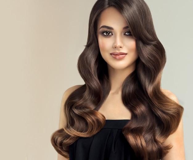 優れた髪の波長い巻き毛の手入れの行き届いた髪型の若い茶色の髪の美しいモデル